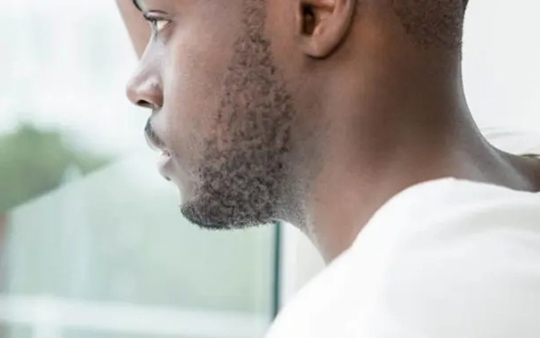 young man staring out the window