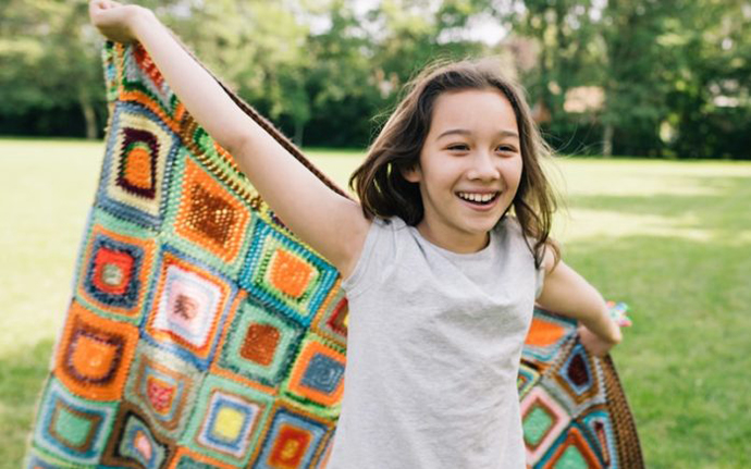 young girl waving a blanket in a park