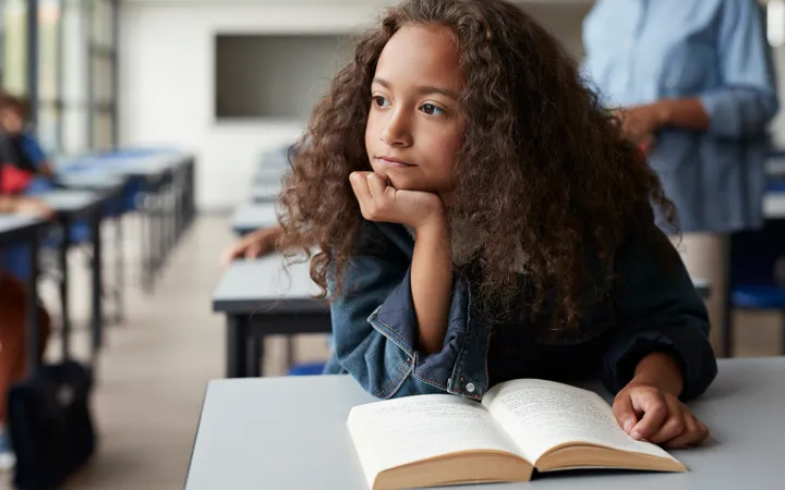 young biracial girl in a classroom. photo by Klaus Vedfelt