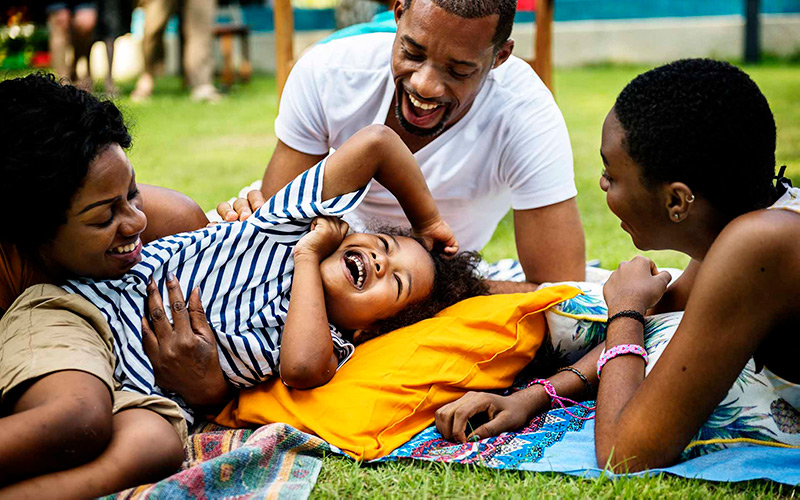 three Black adults playing outdoors with a child