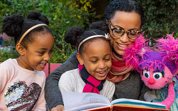 two little girls, a woman and a sesame street character reading a book